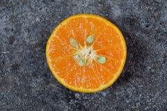 Thailändisches friut - orange Schnitt im Heft oder in orange Scheibe lokalisiert auf schwarzem Zementhintergrund stockfoto
