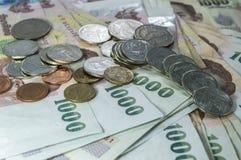 Thailändisches Geld, 1000 Bahtbanknoten und Münze auf weißem Hintergrund Stockfotos