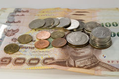 Thailändisches Geld, 1000 Bahtbanknoten und Münze auf weißem Hintergrund Lizenzfreie Stockfotos