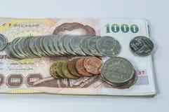 Thailändisches Geld, 1000 Bahtbanknoten und Münze auf weißem Hintergrund Stockfotografie