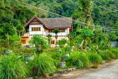 Thailändisches Haus mit Palmen Stockfotos