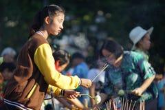Thailändisches Mädchen bereitet brennenden Weihrauch für das Beten während Songkhran vor stockbild