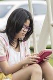 Thailändisches Mädchen, das mit digitaler Tablette sich entspannt Lizenzfreie Stockbilder