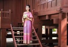 Thailändisches Mädchen kleidet thailändisches traditionelles Kostüm an traditionellem thailändischem Lizenzfreie Stockbilder