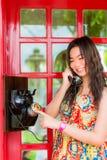 Thailändisches Mädchen spricht mit einem Altmodetelefon Lizenzfreie Stockfotos