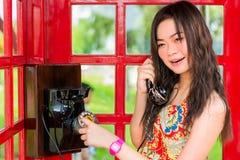 Thailändisches Mädchen spricht mit einem Altmodetelefon Lizenzfreies Stockbild