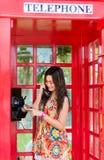 Thailändisches Mädchen spricht mit einem Altmodetelefon Lizenzfreies Stockfoto