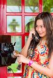 Thailändisches Mädchen spricht mit einem Altmodetelefon Stockfoto