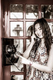 Thailändisches Mädchen spricht mit einem Altmodetelefon im Schwarzen und im Whit Lizenzfreie Stockfotografie