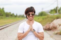 Thailändisches männliches jugendlich in der Sonnenbrille und im weißen T-Shirt ist lächelnd durchführend und thailändischen Gruß stockfotografie