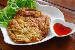 Thailändisches Omelett mit Chili-Sauce auf Herz-förmiger weißer Platte Stockbild