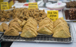 Thailändisches traditionelles Lebensmittel Fried Tofu auf Stahlgitter an der thailändischen Marktart mit einer gelben Karte des N Stockfoto