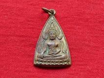 Thailändsk amulett, på röd bakgrund Arkivfoto