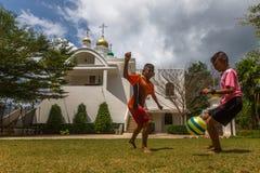 Thailändsk barnlek i boll nära den ryska ortodoxa kyrkan Royaltyfri Bild