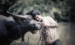 Thailändsk bonde med buffeln arkivbild