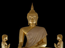 Thailändsk Buddhastaty mot en svart bakgrund Arkivbild