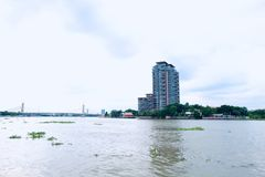 Thailändsk flodstrandandelsfastighet bak bron fotografering för bildbyråer