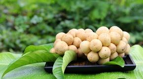 Thailändsk frukt, Lansium domesticum på trämagasinet Arkivfoton