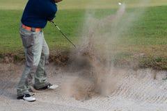 Thailändsk golfspelare för ung man i handlinggunga i sandgrop under övning för golfturnering på golfbanan royaltyfri bild