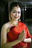 Thailändsk kinesisk dam i röd klänninghälsningvälkomnande arkivbilder