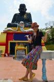 Thailändsk kvinna för stående med den största statyn av Luang Pu Thuat Royaltyfri Bild