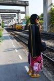 Thailändsk kvinna för stående med drevet på järnväg på Thail arkivfoto