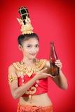 Thailändsk kvinna med en flaska av drinken Arkivfoto