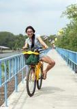 Thailändsk kvinna som rider en cykel arkivbild