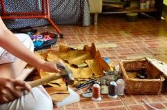 Thailändsk kvinna som stansar hålet på läder för gjort handgjort påseläder Royaltyfri Fotografi