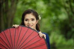 Thailändsk kvinnastående med röd umbella under gummiträden Arkivbilder