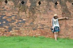 Thailändsk kvinnastående på bakgrund för tegelstenvägg av befästningen i Kanchanaburi Thailand Royaltyfria Foton