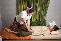 Thailändsk massös som gör massagen för livsstilkvinna i brunnsortsalong Asiatisk härlig kvinna som får thailändsk växt- massageko royaltyfri foto