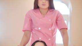 Thailändsk massageperiod Ung kvinna som sitter och tycker om skuldramassagen av en annan kvinna le lager videofilmer