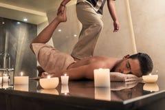 Thailändsk massagepraktiker som masserar mannen till och med sträckning av techn arkivbilder