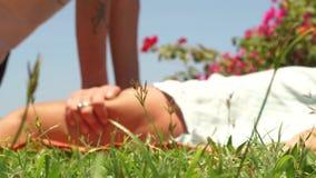 Thailändsk massagiste som gör trängande massage till kvinnan, lägger benen på ryggen utomhus- Manmassagist som gör yogamassagen f lager videofilmer