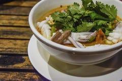 Thailändsk mat - kryddig soppagarnering för tioarmad bläckfisk med koriander i den vita bunken på träskrivbordet, läcker matställ royaltyfri fotografi