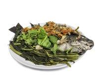 Thailändsk mat och att ånga Tilapiafisken och strimmigt griskött häller med rött Arkivfoto