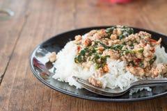 Thailändsk mat, ris som överträffas med stekt under omrörning griskött, och basilika Arkivfoto