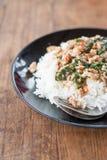 Thailändsk mat, ris som överträffas med stekt under omrörning griskött, och basilika Arkivbilder