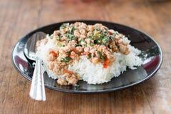 Thailändsk mat, ris som överträffas med stekt under omrörning griskött, och basilika Royaltyfri Foto
