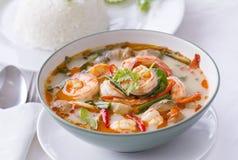 Thailändsk mat, Tom Yam Goong, i vit med ångade ris Arkivbild