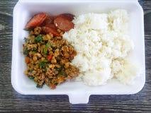 Thailändsk matstil, ris överträffade med uppståndelse stekt finhackat griskött med heliga basilikasidor och den stekte korven i s arkivbilder