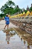 Thailändsk mauhom för kvinnakläder beklär ståenden med den buddha statyn Arkivbild