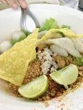 Thailändsk nudel ingen soppaserve med ägget, citron och grisköttboll och toppningar med kryddigt thai matgata Royaltyfria Bilder