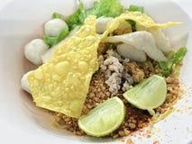Thailändsk nudel ingen soppaserve med ägget, citron och grisköttboll och toppningar med kryddigt thai matgata Arkivbild