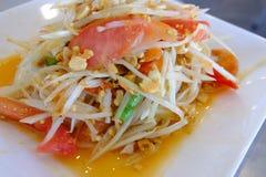 Thailändsk papayasallad eller SomTum på den vita färgmaträtten, traditionell kryddig thailändsk mat Selektivt fokusera arkivbild