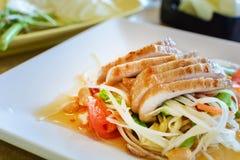 Thailändsk papayasallad på den vita maträtten med grillat griskött Arkivbilder