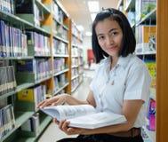 Thailändsk student för ung kvinna som läser en bok Arkivfoton