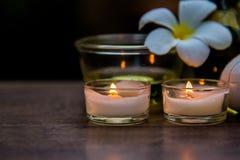 Thailändsk terapi för arom för brunnsortsammansättningsbehandlingar med stearinljus och Plumeria blommar på trätabellen arkivbild