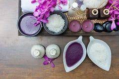 Thailändsk terapi för Spa behandlingarom saltar, och natursocker skurar och vaggar massage med orkidéblomman på trä med stearinlj arkivfoto